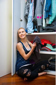 Teen girl choosing clothes in front of closet — Stock Photo