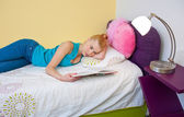 Teen girl reading book in bed — Stok fotoğraf