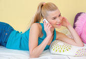 Teen girl talking to mobile phone in her room — Stock Photo