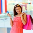 Woman with shopping bags holding credit card — Stock Photo #48887129