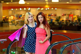 Two woman friends in shopping mall — Stock Photo