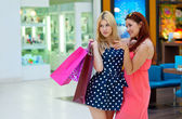 Two woman friends in shopping mall with bags — Stock Photo