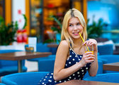 Attractive teen girl drinking juice in bar — Stock Photo