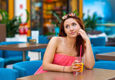 Attractive teen girl drinking juice in bar — Stockfoto