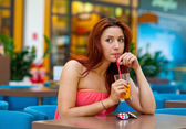 Attractive girl drinking juice in bar — Stock Photo