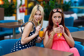 Two woman friends drinking juice in bar — Stock Photo
