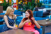 Two woman friends drinking juice in bar — Stock fotografie