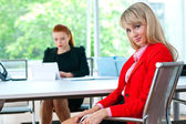 Attractive business woman in office with colleague in background — Stockfoto