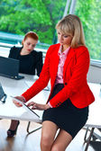 Business woman working on tablet with colleague in background — Zdjęcie stockowe