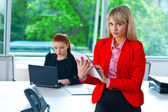 Business woman working on tablet with colleague in background — Stockfoto