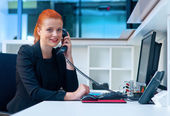 Attractive business woman in office on phone — Stockfoto