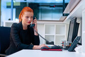 Attractive business woman in office cubicle on the phone — Stock Photo