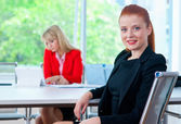 Attractive business woman in office with colleague in background — Stock Photo