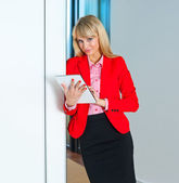 Business woman in office corridor with tablet computer — Stockfoto