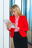 Business woman in office corridor with tablet computer — Stock Photo