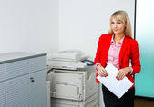 Business woman with documents standing next to printer — Stock Photo