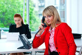 business woman talking to phone with colleague in background — Stock Photo