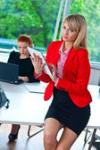 Business woman working on tablet with colleague in background — Stock Photo