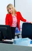 Attractive business woman in office with computer — Stockfoto