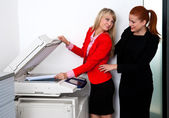 Two woman colleagues working on printer in office — Stock Photo