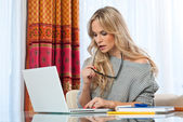 Attractive blond woman writing on laptop — Foto de Stock