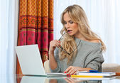 Attractive blond woman writing on laptop — Stock Photo
