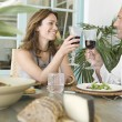 Mature couple toasting with red wine while having lunch at their vacation home. — Stock Photo