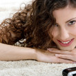 Woman laying down on a furry carpet at home — ストック写真