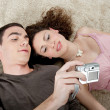Portrait of two young laying down on a fury carpet at home — Stockfoto