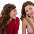 Two young women sharing their earphones and listening to music — Stock Photo
