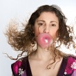 Stock Photo: Close up portrait of young womblowing strawberry bubble gum while her hair flies in air, isolated against plain background.
