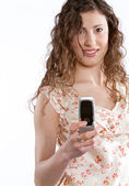 Young woman holding a cell phone in her hand while dialing — Stock Photo