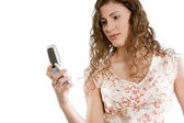 Young woman holding a cell phone in her hand — Stock Photo
