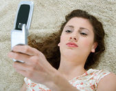 Woman laying down on a furry carpet at home, using a cell phone — Stock Photo