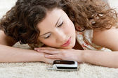 Woman laying down on a furry carpet at home — Zdjęcie stockowe