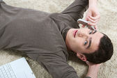 Teenage boy having a cell phone conversation while laying down on a furry carpet — Stock Photo