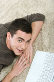 Man laying down on a furry carpet at home — Stock Photo