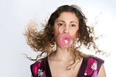 Close up portrait of a young woman blowing a strawberry bubble gum while her hair flies in the air, isolated against a plain background. — Stock Photo