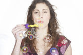 Portrait of teenager blowing bubbles towards the camera. — Stock Photo