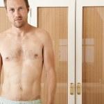 Attractive man in front of wardrobe doors in a bedroom in underwear, smiling. — Stock Photo