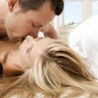 Young couple passionately kissing in bed. - Stock Photo