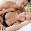 Romantic couple in bed, with man caressing woman's hair. - Stock Photo