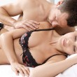 Romantic couple in bed, with man kissing woman's shoulder. - Stock Photo