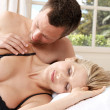 Romantic couple in bed, with man caressing woman's shoulder. — Stock Photo #19804239