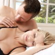 Romantic couple in bed, with man caressing woman's shoulder. - Stock Photo