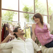 Woman offering a newly bought gift to her boyfriend in fashion store. — Foto de Stock