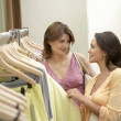 Two girlfriends looking at clothes in a fashion store. — Stockfoto #19804991