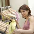 Woman looking at line of clothes hanging in a fashion store. — Stock Photo