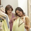 Two girlfriends looking at clothes in a fashion store. — Stock Photo