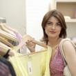 Young woman holding a garmet in a fashion store. — Stock Photo